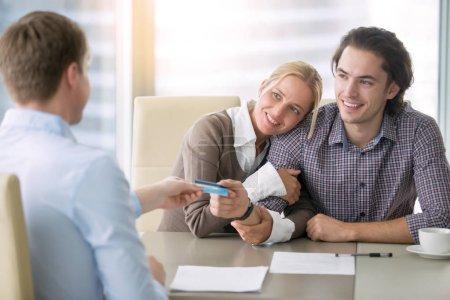 Young happy couple paying with card
