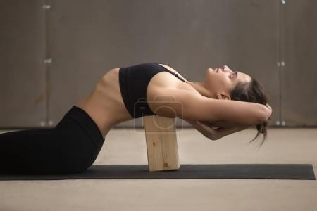Photo for Young attractive sporty woman practicing yoga, stretching in Matsyasana using wooden block, Fish pose, exercise for spine and shoulders flexibility working out, cool urban style, grey studio, closeup - Royalty Free Image