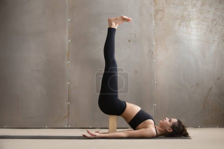 Photo for Young attractive yogi woman practicing yoga, standing in Viparita Karani exercise, using wooden block, working out, wearing black sportswear, cool urban style, full length, grey studio background - Royalty Free Image