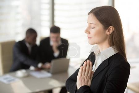 Photo for Young beautiful businesswoman enjoys meditating standing in office with eyes closed, put hands together as in prayer, reduce stress, relief to keep calm, positive thinking, appeasement, autosuggestion - Royalty Free Image