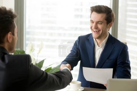 Happy excited business partners handshaking after signing mutual
