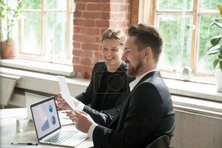 Photo pour Deux dirigeants satisfaits discutent de la croissance de l'entreprise succès du projet statistiques financières avec des graphiques en hausse sur écran d'ordinateur portable, homme d'affaires détenant un document montrant des statistiques croissantes à partenaire dans le bureau - image libre de droit