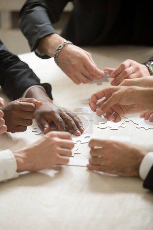 Foto de Grupo multiétnico de gente armar rompecabezas juntos, las manos unir piezas en escritorio, concepto exitoso trabajo en equipo, equipo, actividad, ayuda y apoyo en negocios, cerca de vista vertical - Imagen libre de derechos