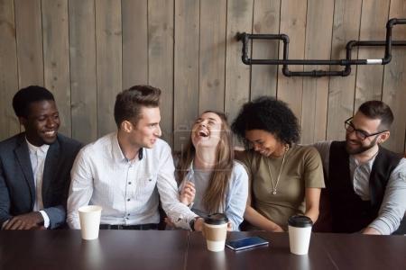 Photo pour Jeune homme plaisantant à la réunion de café faire rire des amis multiraciaux, diverses personnes guffaw après gars racontant drôle histoire comique pendant la pause café, heureux compagnons noirs et blancs s'amuser dans le café - image libre de droit