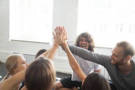 Photo pour Groupe de jeunes gens sportives donnant une haute cinq, gifler les paumes des mains posées dessus, Bravo concept, l'équipe formation d'esprit, plaisir et motivation, geste de victoire ou de la célébration - image libre de droit