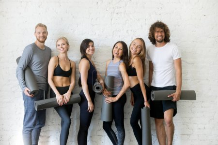 Group of young sporty people standing at the white wall