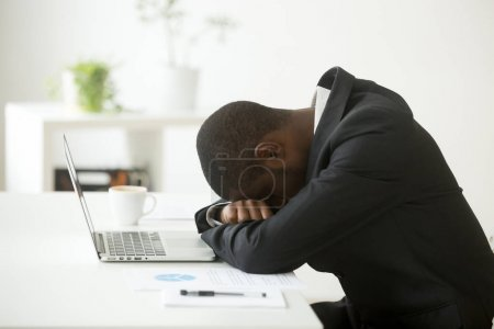 Photo for African-american tired deprived businessman feeling lack of sleep having nap at workplace, black restless entrepreneur hopeless by bankruptcy or debt, depressed investor desperate about failure - Royalty Free Image