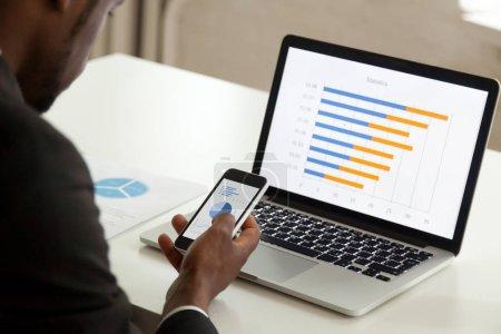 Photo pour Homme d'affaires afro-américain utilisant des appareils pour les entreprises, travailleur de bureau noir tenant smartphone travaillant avec ordinateur portable et téléphone mobile, applications statistiques d'entreprise et des logiciels, sur la vue d'épaule - image libre de droit