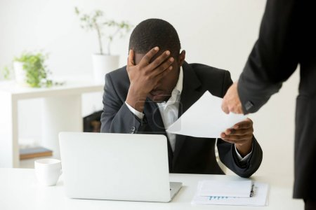 Photo for Frustrated upset african american office employee receiving dismissal notice at workplace, depressed bankrupt black entrepreneur getting fired from work, distraught by notification warning about debt - Royalty Free Image