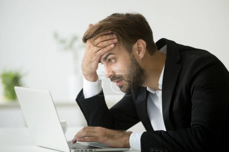 Photo for Worried stressed businessman in suit shocked by bad news using laptop at work, desperate bankrupt investor lost money online depressed by financial problem debt, frustrated worker tired of overwork - Royalty Free Image