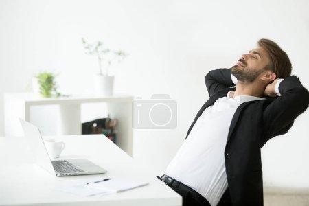 Photo pour Succès jeune homme d'affaires en costume relaxant sur le lieu de travail avec ordinateur portable fini de travail, employé calme détendu se sent heureux respirant l'air frais, souriant ceo bénéficie pause dans le bureau, aucun soulagement sans stress - image libre de droit
