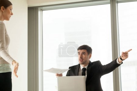 Photo for Angry CEO with report in hand pointing on door, asking to leave responsible for financial mistakes female office worker, guilty woman looking on boss with confusion. Firing because of bad work results - Royalty Free Image