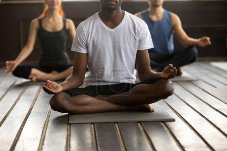 Photo pour Jeune homme noir et un groupe de personnes sportives pratiquant des cours de yoga avec instructeur, assis dans l'exercice Sukhasana, pose Easy Seat avec geste mudra, séance d'entraînement, gros plan intérieur, étage du studio - image libre de droit