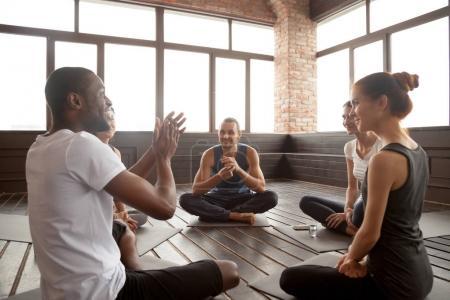 Foto de Excitado el hombre del afroamericano hablando a deportivos amigos diversos felizes sentado en la estera en estudio, instructora de yoga negro feliz o vida entrenador motivando gente joven divirtiéndose en clase de seminario - Imagen libre de derechos