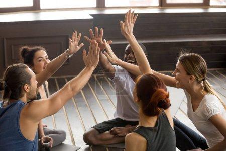 Photo pour Ayant à l'esprit heureux sportifs divers peuples joindre les mains ensemble au séminaire du groupe assis sur des nattes en studio, excité fit amis donnent cinq haute supportant le mode de vie sain et l'unité dans le concept d'objectifs de remise en forme - image libre de droit