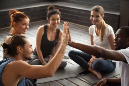 Photo pour Fit sportifs souriants africains et Caucasiens hommes donnant cinq élevés à la formation de groupe, motivés divers amis multiraciales réunir mains comme concept d'équipe de soutien au travail d'équipe de fitness yoga studio - image libre de droit