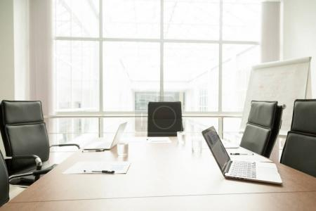 Photo for Conference table with laptops, documents and chairs in office of modern contemporary business center, big corporate boardroom interior with large window, empty light meeting room work space concept - Royalty Free Image