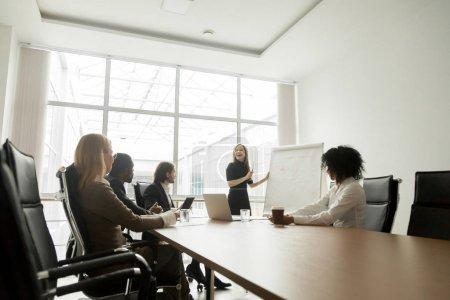 Photo pour Smiling businesswoman donner présentation à divers partenaires dans la salle de réunion, coach d'affaires positif expliquant le nouveau projet au groupe multiracial, chef d'équipe présentant un plan marketing sur tableau blanc - image libre de droit