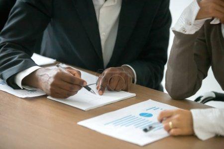 Photo pour Homme d'affaires diversifié et femme d'affaires en collaboration avec statistiques, homme africain dessin graphique expliquant la nouvelle idée pour l'amélioration de la gestion à caucasien collègue, concept de travail d'équipe d'équipe du projet - image libre de droit