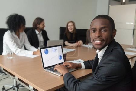 Photo pour Souriant afro-américaine homme d'affaires en costume regardant la caméra à la réunion, analyste à l'aide de portable avec les statistiques de projet à l'écran, gestionnaire noir professionnel au travail portrait de l'équipe diversifiée - image libre de droit