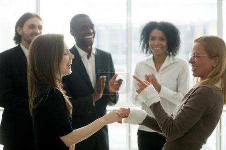 Photo pour Drôles femmes d'affaires souriants, main dans la main, célébrant les succès tandis que divers équipe applaudissant, femelle handshaking exécutif féliciter employé avec l'atteinte des objectifs communs, pouvoir des femmes en affaires - image libre de droit