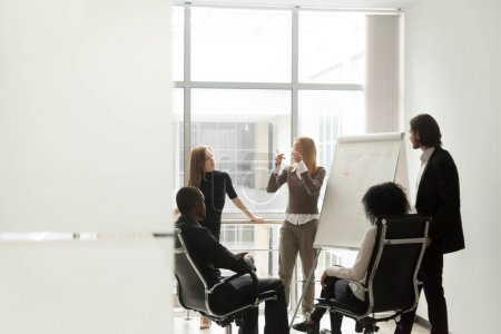 Photo for Diverse business team listening to female speaker discussing presentation on flip chart at meeting in boardroom, group brainstorm and marketing sales coaching corporate training concept, copy space - Royalty Free Image