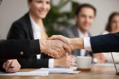 Photo pour Des mains de dirigeants et de jeunes hommes d'affaires serrant la main lors d'une réunion de groupe, deux partenaires d'âge différent se serrant la main pour conclure un accord ou une bonne affaire, conclure un contrat aide à soutenir le concept, vue de près - image libre de droit