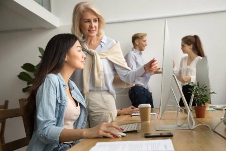 Photo pour Âgés de mentor féminin formation jeune asiatique interne expliquant le travail sur ordinateur, enseignement exécutif amical senior nouvel employé en regardant l'écran pc, anciens parle de professeur à élève aidant avec des tâches en ligne - image libre de droit