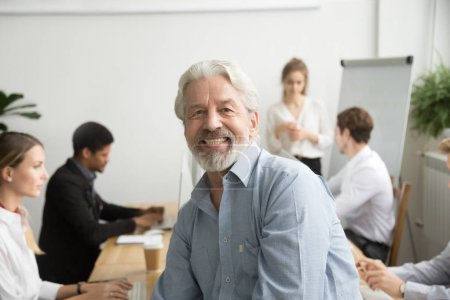Photo for Smiling male senior team leader, aged teacher looking at camera with office people at background, happy old gray-haired company boss, experienced mentor or executive professional head shot portrait - Royalty Free Image