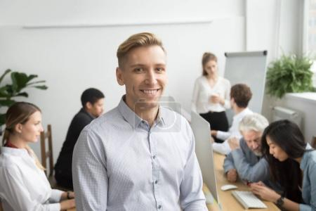 Photo for Smiling young businessman looking at camera with diverse team office people employees at background, business coach, successful team leader or professional executive manager head shot portrait - Royalty Free Image