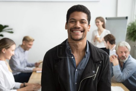 Photo for Smiling african american office employee or leader looking at camera with diverse colleagues at background, happy young black manager, professional coach or team member posing, head shot portrait - Royalty Free Image