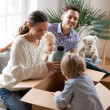 Happy family with two kids unpacking boxes after r...