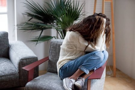Photo for Depressed sad woman holding head in hands sitting on armchair at home, harassment abuse teenage victim feeling bad, heartbroken upset girl crying having mental problem or dangerous drug addiction - Royalty Free Image