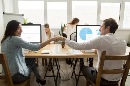 Asian employee fist bumping caucasian colleague sitting in multi