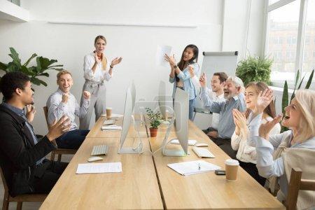 Photo pour Les collègues d'équipe divers entreprise féliciter motivé collègue africain avec succès de l'entreprise ou les réalisations frappant dans les mains dans le Bureau de coworking, multiraciales employés applaudissent excité par la bonne nouvelle - image libre de droit