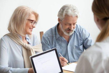 Photo pour Heureux couple de personnes âgées sur le point de signer le document à la réunion avec le conseiller financier, homme plus âgé s'engage à apposer la signature sur le contrat faire achat d'investissement, en tenant d'assurance, âgée de la famille au Bureau des voyages - image libre de droit