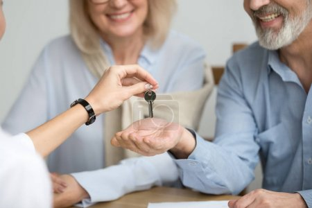 Realtor giving senior couple key to new house at meeting