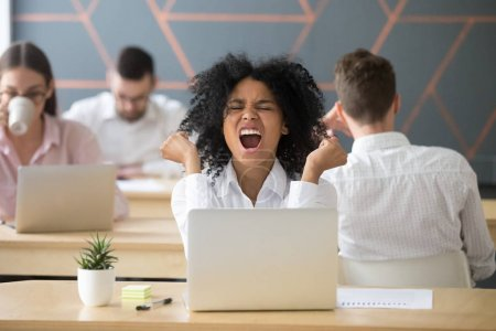 Photo for Excited african american employee celebrating online win, great deal or business success feeling ecstatic sitting with laptop in coworking office, happy funny black female student enjoys good results - Royalty Free Image