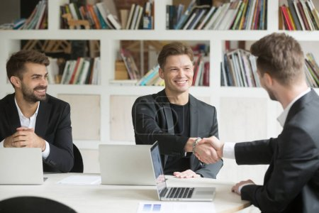 Photo for Male CEO welcoming new colleague by handshake sitting at conference table in modern office brainstorming and discussing company projects. Successful partnership, concept of teamwork, cooperation - Royalty Free Image