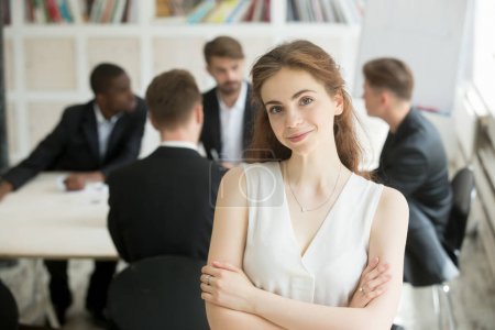 Photo pour Chef de l'équipe féminine séduisante regardant caméra, des collègues de négociation à l'arrière-plan. Portrait de femme d'affaires réussie pose avec les bras croisés. Femmes dans le concept de réussite professionnelle et personnelle - image libre de droit