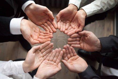Foto de Equipo personas unen manos en palmas círculo arriba como concepto de atención protección, contribución en el crecimiento de crecimiento de negocio y puesta en marcha, enganing crowdfunding, unidad, concepto de confianza o seguridad, cerrar la vista superior - Imagen libre de derechos