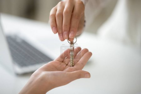 Photo for Female hand holding key, woman getting real estate ownership, customer buying new lease rental house becoming first time home owner, property purchase, mortgage investment loan concept, close up view - Royalty Free Image