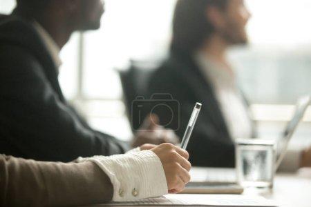 Photo pour Femme tenant un stylo à la main prenant des notes lors de la réunion ou des négociations, femme d'affaires participant à la rédaction d'informations participant à un atelier de formation d'entreprise ou un séminaire éducatif concept, vue de près - image libre de droit