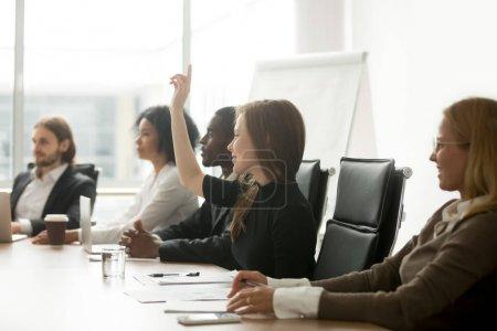 Photo pour Souriant curieuse jeune femme d'affaires levant main à réunion se livrant à du groupe multiracial offert activité, voté en tant que bénévole ou poser question à la formation d'entreprise, séminaire ou atelier - image libre de droit
