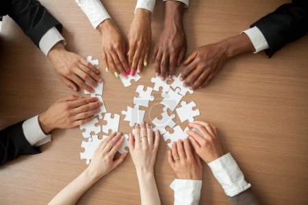 Photo pour Mains de diverses personnes se connectant puzzle ensemble sur le bureau, l'équipe multiethnique s'engageant à trouver les meilleures solutions d'affaires pour succès teamwork, concept de l'unité de teambuilding, haut bouchent avec vue - image libre de droit