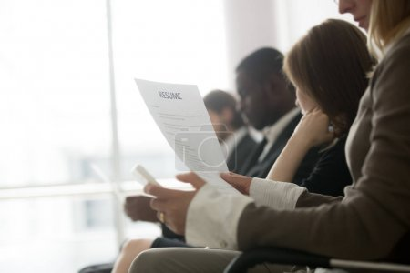 Photo for Multiracial business people waiting in queue preparing for job interview concept, diverse unemployed vacancy applicants holding reading cvs getting ready, human resources concept, focus on resume - Royalty Free Image