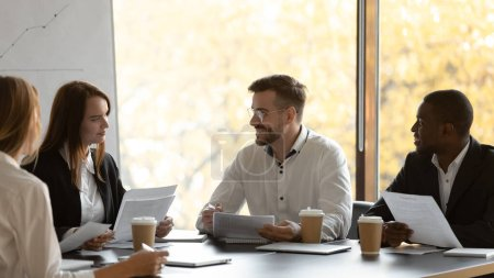Millennial multiracial businesspeople consider paperwork in office