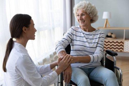Photo pour Soins infirmiers soignante tenir la main soutien handicapé femme âgée patient assis sur fauteuil roulant à l'hôpital à la maison, jeune médecin soignant aider paralysé vieille mamie en fauteuil roulant, concept de soins à domicile senior - image libre de droit