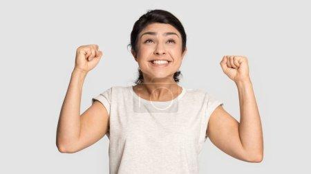 Photo pour Excité réjoui jeune femme indienne célébrant la victoire de loterie, montrant oui geste de près isolé sur fond de studio gris, heureux heureux heureux gagnant belle fille se réjouissant triomphe - image libre de droit