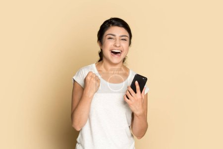 Photo for Excited happy Indian girl celebrating online win, holding phone, looking at camera isolated on brown background, overjoyed successful lucky young woman rejoicing victory, triumph, laughing - Royalty Free Image